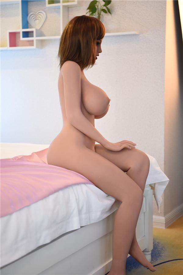 Sexpuppe sitzt am Bett Vivien
